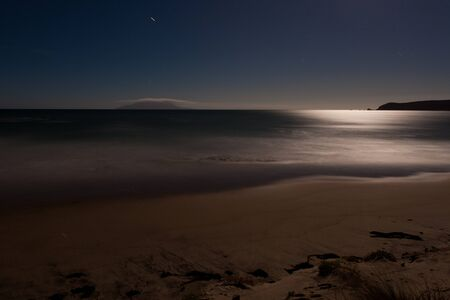 nightscene: Long exposure shot of romantic sand beach lit by the moon, the light of which being reflected on ocean surface Stock Photo