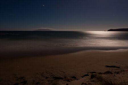 Une longue exposition a tiré de plage de sable romantique éclairée par la lune, la lumière de ce qui se reflète sur la surface de l'océan Banque d'images - 13957717