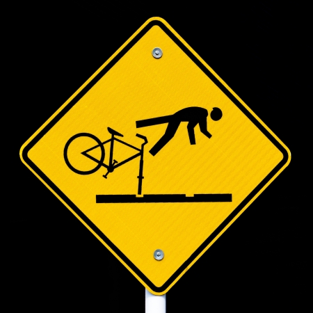 Road sign warning cyclists of dangerous tram tracks isolated on black background. photo
