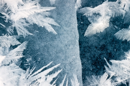 hoarfrost: Cracked ice surface of thick ice layer on lake with beautiful large hoar-frost ice crystals Stock Photo