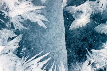 Gebarsten ijs oppervlak van dikke laag ijs op het meer met mooie grote rijp ijskristallen Stockfoto