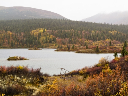 Abandoned wilderness campsite at lake in fall surrounded by beautiful colorful boreal forest wilderness of Yukon Territory, Canada photo