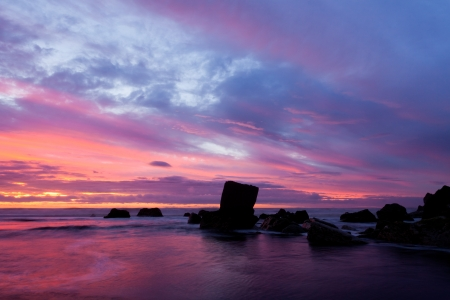 vividly: Dramatic cloudscape of vividly colored sunset over deserted beach and ocean with silhouettes of boulder rocks Stock Photo