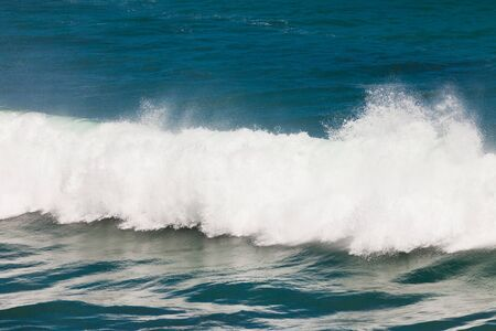 Closeup background of turbulent water of breaking ocean wave and spray on incoming ocean surf photo