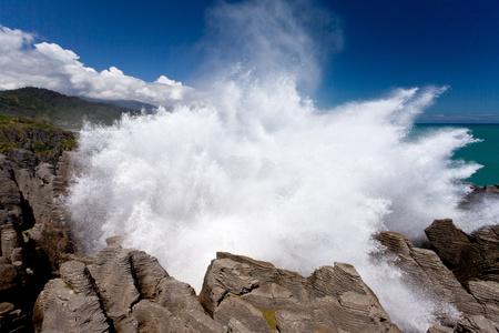 orificio nasal: Surf Mar de Tasmania de la explosi�n en el orificio de respiraci�n en las rocas de la crepe en Punakaiki, Isla Sur, Nueva Zelanda, llevando agua salada salpique fuera de respiraderos de alta en el cielo azul.