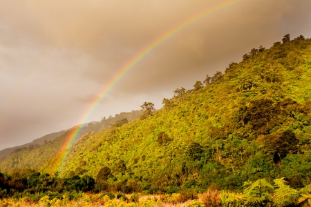 Rainbow glowing over foothills of New Zealands South Islands West Coast adding colored shades to the shrubs and brush after rain storm Stock Photo