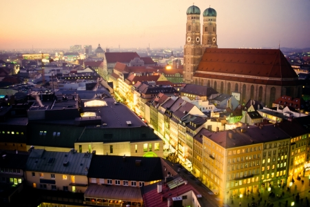 Cathedral of Our Dear Lady, Frauenkirche, in Munich, Germany, Europe, at dusk with illuminated surrounding buildings and a soft suffused sunset Stock Photo