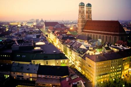 Kathedraal van Onze Lieve Vrouwe, Frauenkirche in München, Duitsland, Europa, in de schemering met verlicht omliggende gebouwen en een zachte overgoten zonsondergang Stockfoto