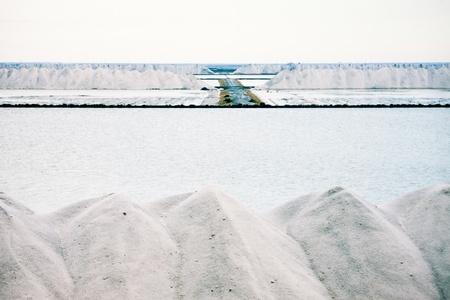 Piles of crystallised salt at saltworks saline refinery where seasalt is purified to give sodium chloride, or table salt