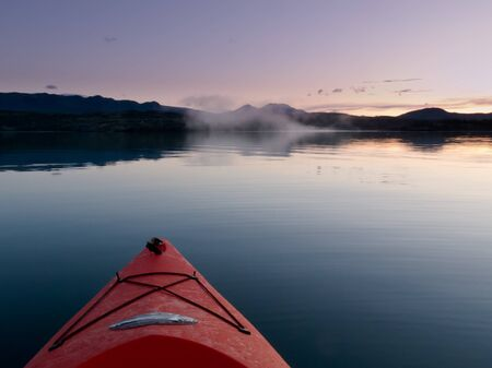 canoeist: View from the perspective of the canoeist of paddling in a kayak through still sunset waters