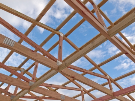 roof framework: Roof frame under construction showing the wooden joists, trusses and beams against a cloudy blue sky Stock Photo
