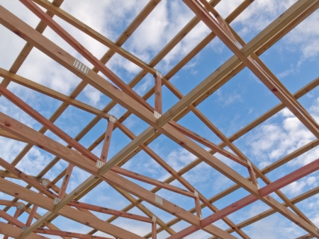 Roof frame under construction showing the wooden joists, trusses and beams against a cloudy blue sky Stockfoto