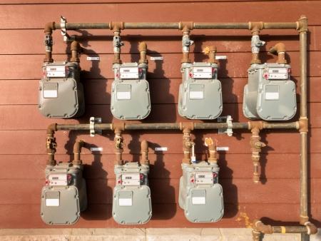 Bank van de individuele residentiële aardgas meter op het opbouwen van buiten naar de consumptie van huishoudens te meten Stockfoto