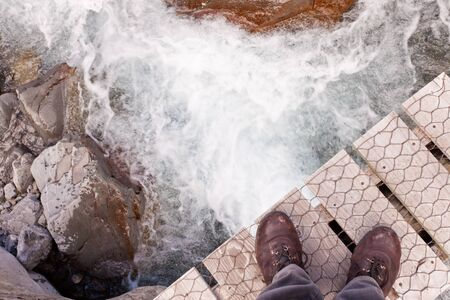 Booted feet of man standing at the edge of a narrow wooden bridge over clear fresh white water rushing through a rocky gorge photo