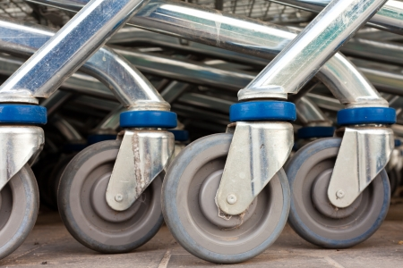 Wheels of shiny metal shopping carts stacked in a row. photo