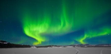 natural light: Luces del Norte (Aurora Borealis) a lo largo de la luna iluminaba paisaje nevado lago congelado y colinas boscosas.
