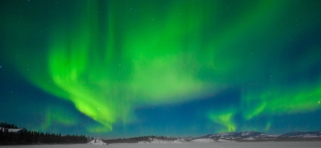aurora borealis: Northern Lights (Aurora borealis) over moon lit snowscape of frozen lake and forested hills.