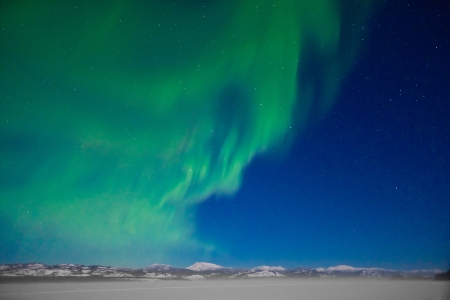 ionosphere: Northern Lights (Aurora borealis) over moon lit snowscape of frozen lake and forested hills.