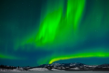 polar light: Luces del Norte (Aurora Borealis) a lo largo de la luna iluminaba paisaje nevado lago congelado y colinas boscosas.