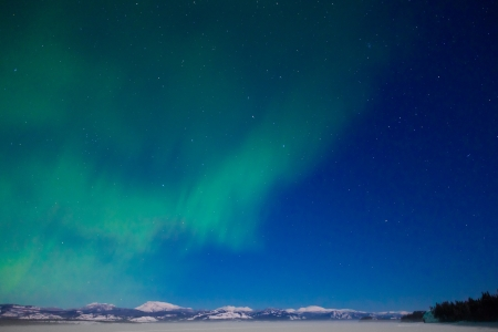 Northern Lights (Aurora borealis) over moon lit snowscape of frozen lake and forested hills. Stock Photo - 14088561