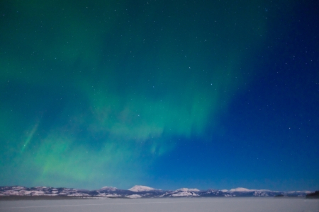 natural phenomenon: Northern Lights (Aurora borealis) over moon lit snowscape of frozen lake and forested hills.