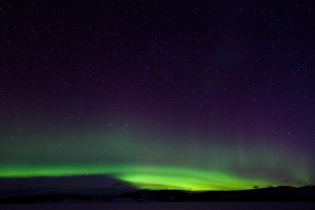 Colorful northern lights (aurora borealis) substorm on dark night sky with myriads of stars. Stock Photo