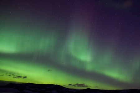 Colorful northern lights (aurora borealis) substorm on dark night sky with myriads of stars. photo