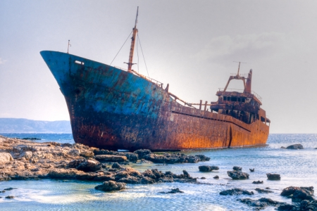Abandoned broken ship-wreck beached on rocky sea shore.