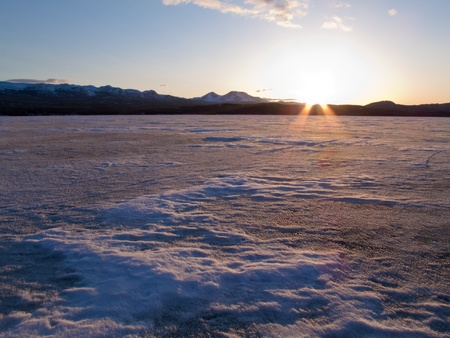 Vast ice surface of huge frozen Lake Laberge,  Yukon Territory, Canada, in April photo