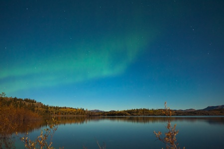 Northern lights (Aurora borealis) in moonlit night over Lake Laberge, Yukon, Canada, in fall. photo