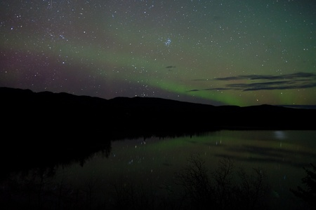 Night Sky Stars with faint Northern Lights mirrored on calm lake in Yukon, Territory, Canada. photo