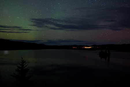 whitehorse: Night Sky Stars, clouds and faint Northern Lights over dark road at lake shore, Yukon, Territory, Canada.