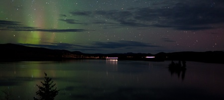 Night Sky Stars, clouds and faint Northern Lights over dark road at lake shore, Yukon, Territory, Canada.