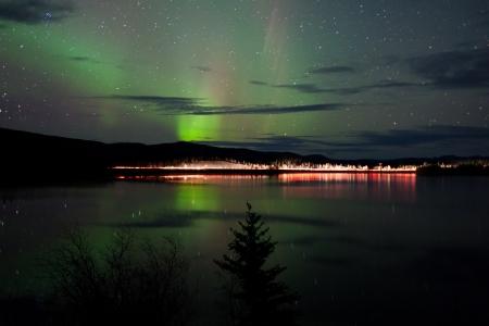 aurora borealis: Night Sky Stars, clouds and Northern Lights over country road at lake shore, Yukon, Territory, Canada.