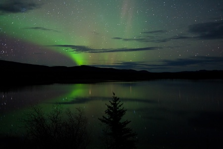 Night Sky Stars, clouds and Northern Lights mirrored on calm lake in Yukon, Territory, Canada. photo