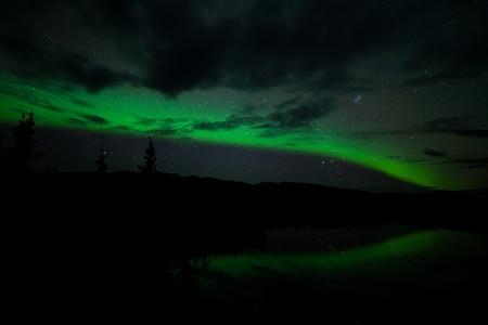 magnetosphere: Stelle cielo notturno, nuvole e Northern Lights riflette sul lago tranquillo in Yukon, Territory, Canada.