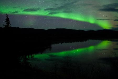 magnetosphere: Stars Night Sky, nubi e Northern Lights specchia sul lago tranquillo in Yukon, Territory, Canada.