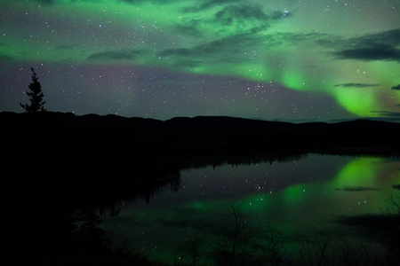 whitehorse: Night Sky Stars, clouds and Northern Lights mirrored on calm lake in Yukon, Territory, Canada. Stock Photo