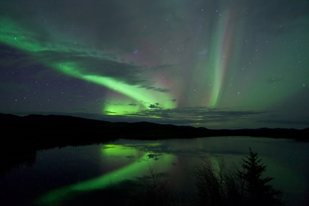 whitehorse: Night Sky Stars, clouds and Northern Lights over country road at lake shore, Yukon, Territory, Canada.