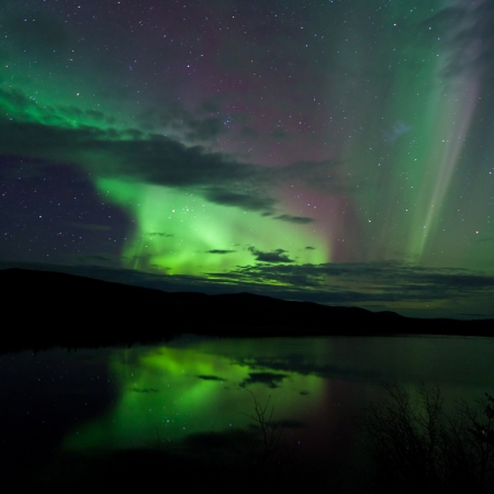 Night Sky Stars, clouds and Northern Lights mirrored on calm lake in Yukon, Territory, Canada. 免版税图像