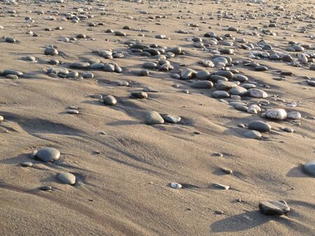 Background texture pattern of pebbles on a sandy water washed tidal beach in evening light photo
