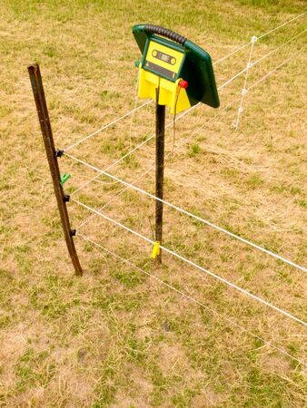 electric fence: Electric fence charger mounted on a pole providing the energy for electrical livestock fencing out on rural farmland