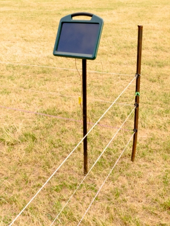 fencing wire: Solar electric fence charger mounted on a pole providing the energy for electrical livestock fencing out on rural farmland