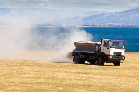 phosphate: Truck spreading fertilizer on pasture meadow creating an enormous white dust cloud of rock phosphate and potash Stock Photo