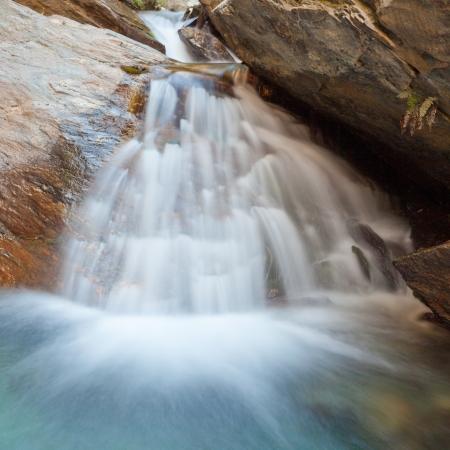 recursos naturales: Pequeña cascada natural casdcading sobre rocas en un estanque azul calma abajo con aspecto sedoso de larga exposición