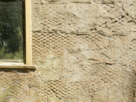 wire mesh: Exterior surface of plastered wall still showing wire mesh underlay support framework built into the structure Stock Photo