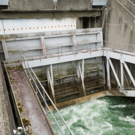 causing: Hydro control structure weir with flow passing underneath causing a violent turbulence discharge of white water