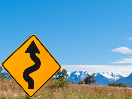 Wavy arrow on road sign pointing upward with beautiful backdrop snowy mountain landscape photo