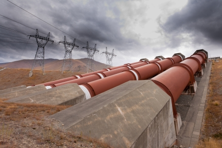 hydroelectricity: Global warming and renewable energy concept, penstock water pipes in a hydroelectric power plant on barren hillside with electric trabsmission line pylons against dramatic stormy sky