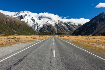 new horizon: Straight empty highway leading into Aoraki-Mount Cook National Park to the highest peaks of the Southern Alps lining the horizon, South Island of New Zealand